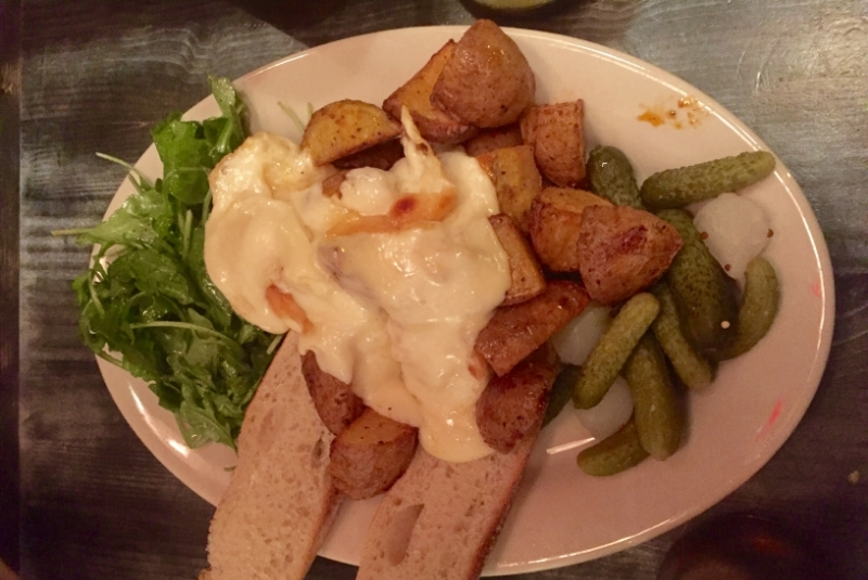 """Dinner from Raclette, """"the melted cheese restaurant,"""" in East Village. They give you a plate of roasted potatoes, bread, pickles, pearl onions, and lightly dressed arugula, then you get three scrapes of this gigantic 1/2 round of melted, creamy raclette cheese on top. It was heaven."""