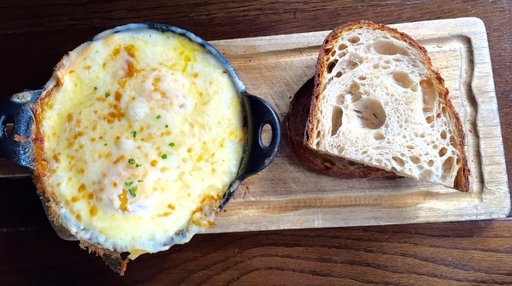 """""""Eggs in Pergatory"""" also from Petite Abeille--a cheesy dish of poached eggs, bechamel sauce, carmelized gruyere and roasted tomatoes underneath. Served with crusty french bread for dipping."""