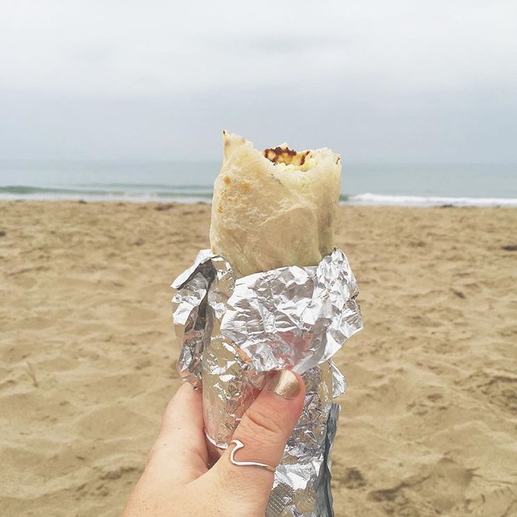 Me, before the proposal, giddy at the beach with my burrito and ring.  Haha!