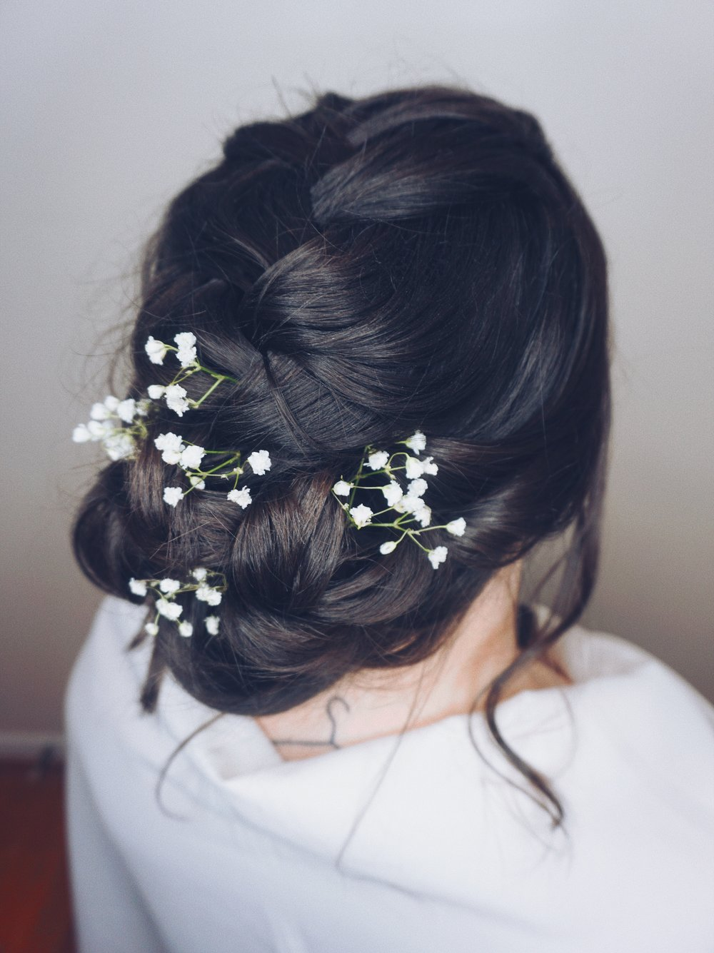 Romantic textured low bun with braids & florals