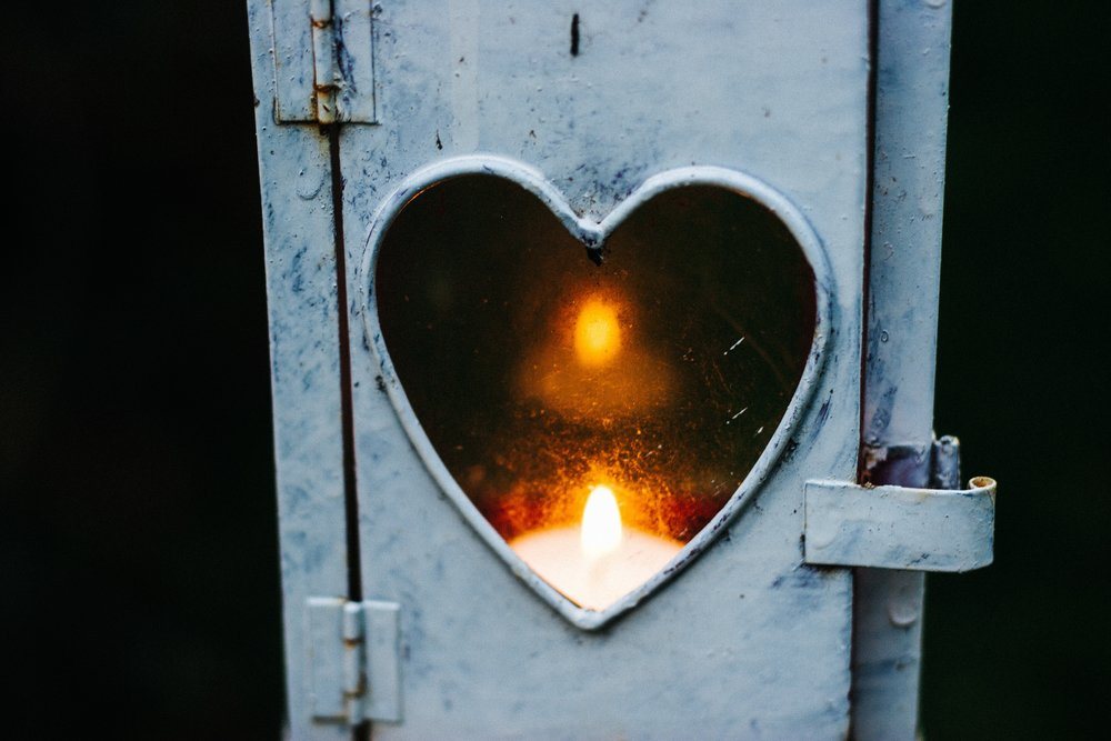 A lit white candle glows and peers out of the heart-shaped window in a metal locked box