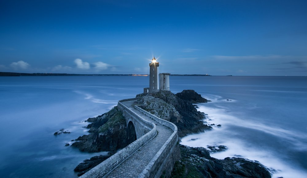 A blue toned picture of a light house at the end of a walled stone pathway