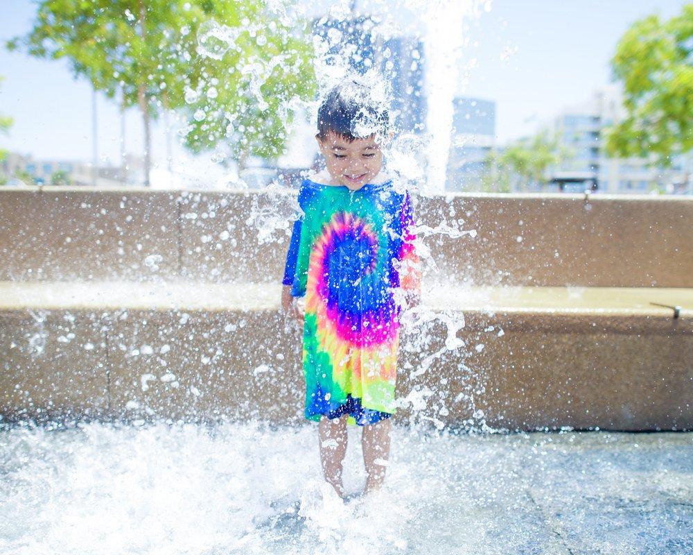 A four-year-old boy has fun splashing in a fountain