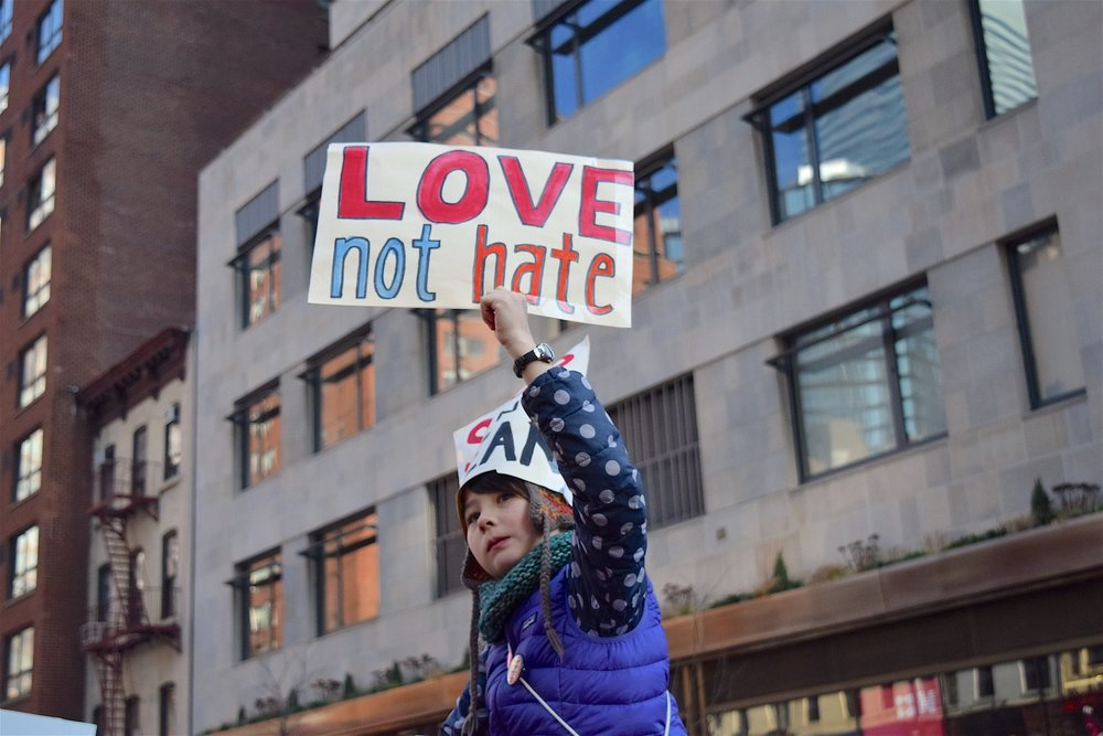Love not hate placard is being held up by a young teenage girl at the Women's March of 2017