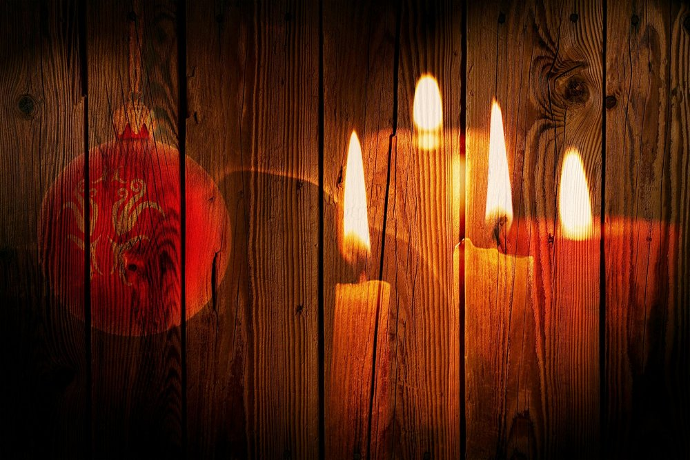 A red Christmas ornament and golden candles superimposed over a wooden wall