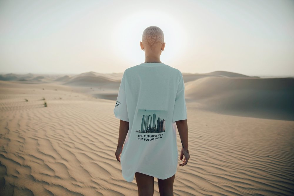 """Empowered woman walks in the desert wearing a shirt that says, """"The Future Is Then, the Future Is Now"""""""