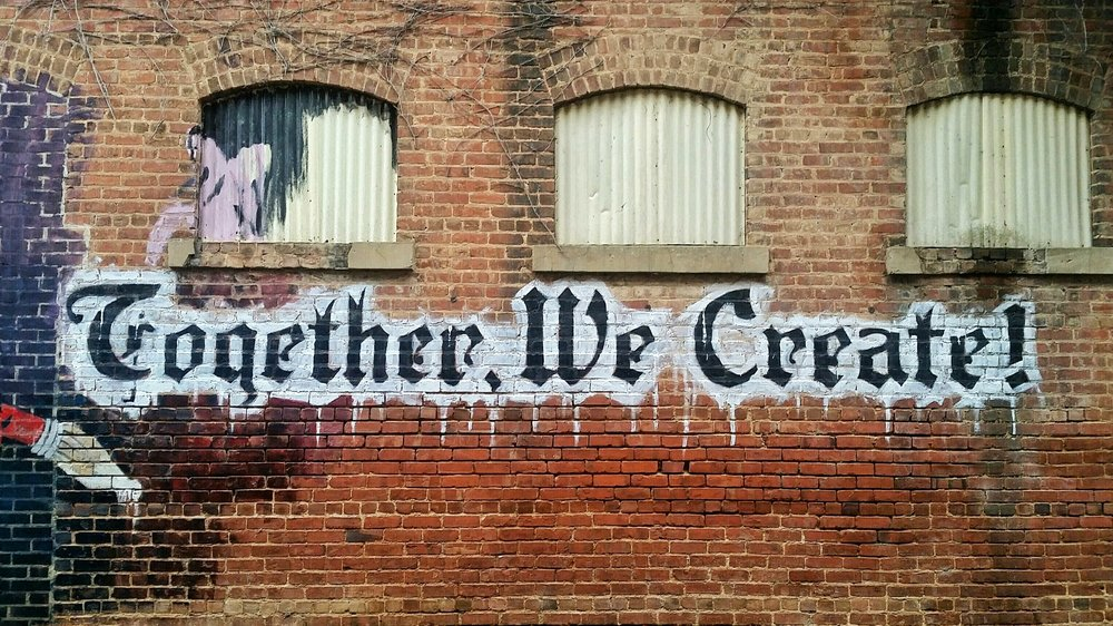 "A graffiti painted wall saying ""Together, We Create!"""