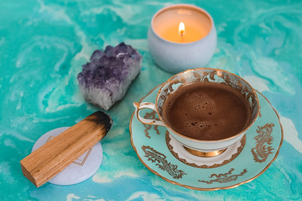 Wood, an amethyst crystal, a burning candle and tea gathered together for sacred ritual