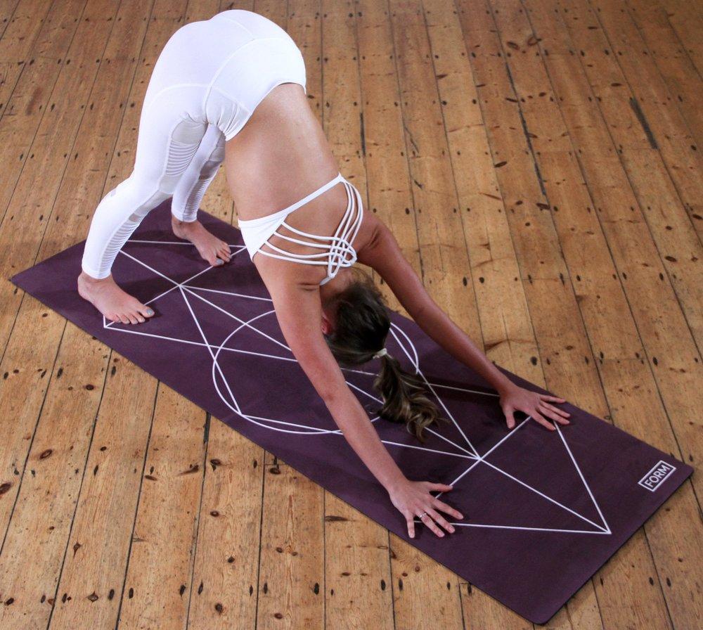 A woman performs downward facing dog yoga pose on a sacred geometry yoga mat