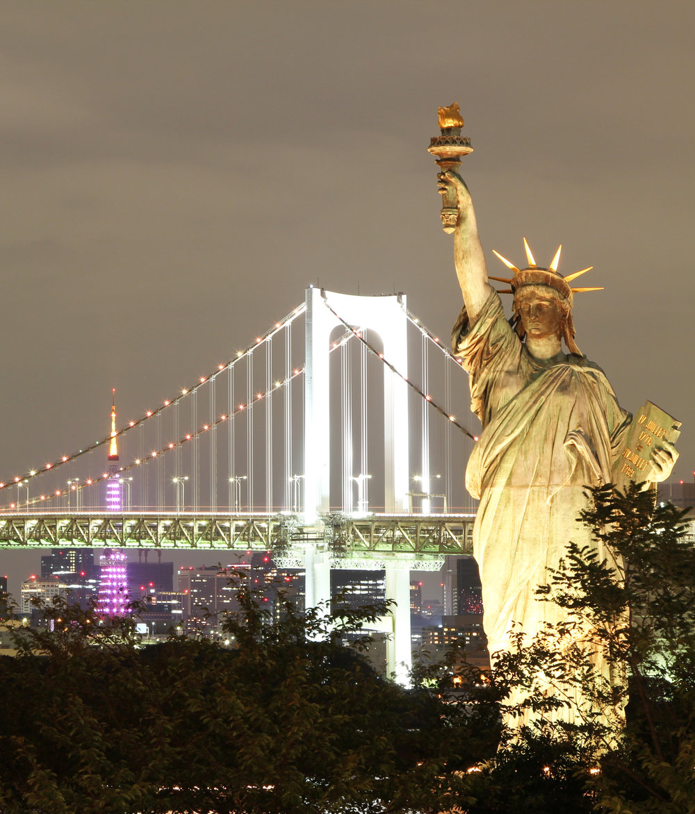 A golden lit statue of liberty at night in the foreground with New York City as backdrop