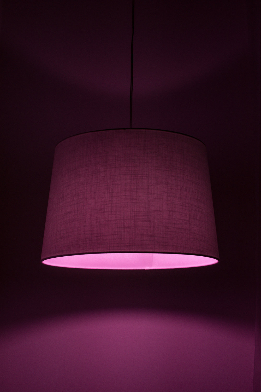 A mulberry colored fabric hanging ceiling lamp illuminates a room of the same color