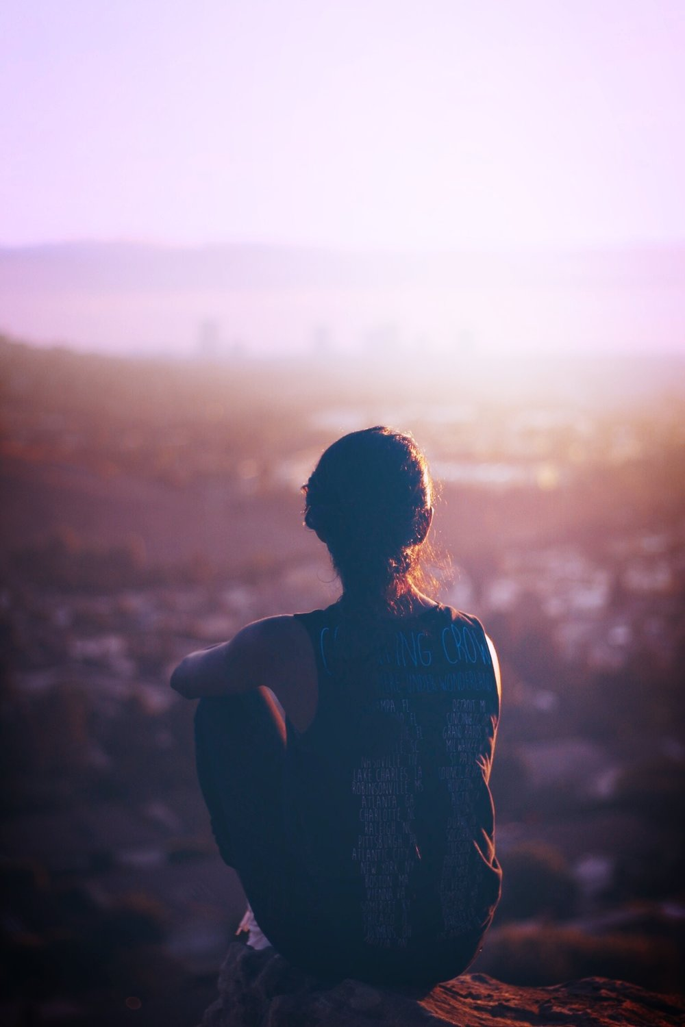 A woman sits on a low cliff overlooking the city at dusk