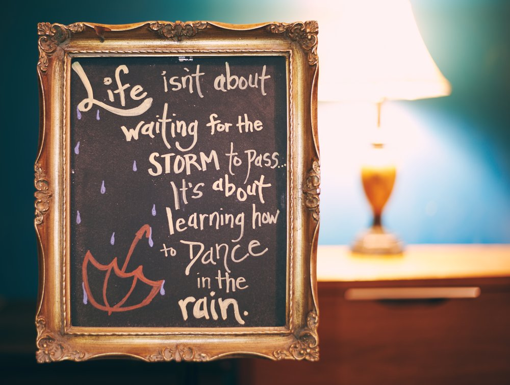 """A framed chalkboard message says, """"Life isn't about waiting for the storm to pass… it's about learning howe to dance in the rain."""""""