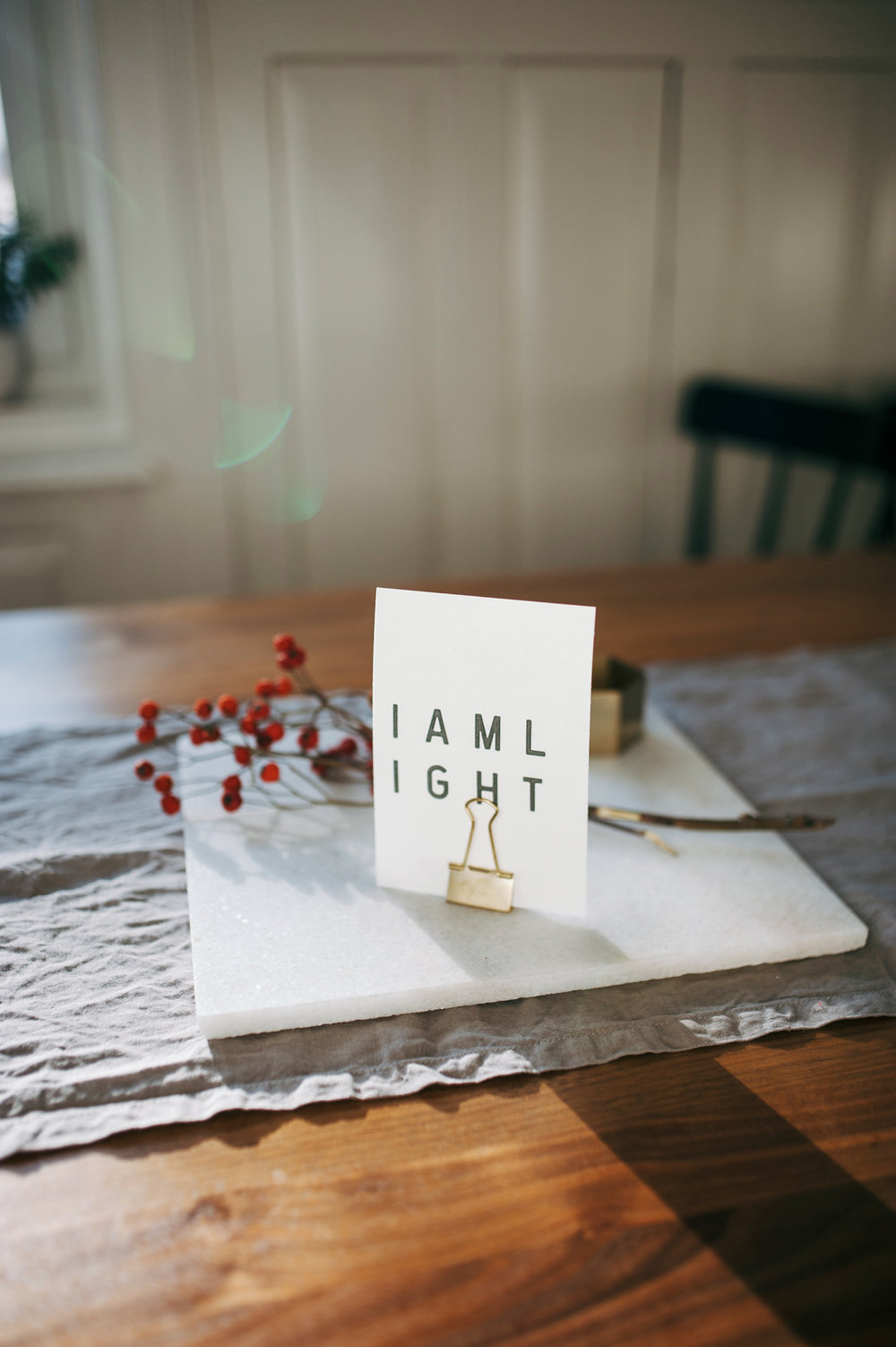 """A dining table features a marble slab with a clip note that says, """"I am light."""""""