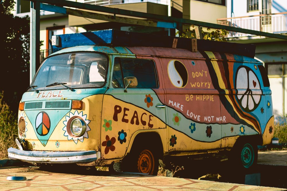 "A van is colorfully painted hippie-style with the words, ""Don't worry, be hippie; Make love not war; and Peace."""