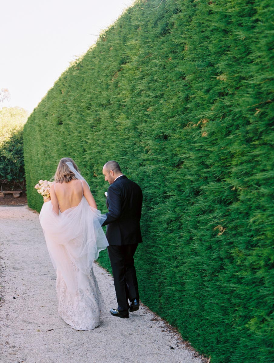 Wedding Photographer Adelaide Bentinmarcs- Carrick Hill Wedding-David Feldon Wedding Dress-couple walking in hedge
