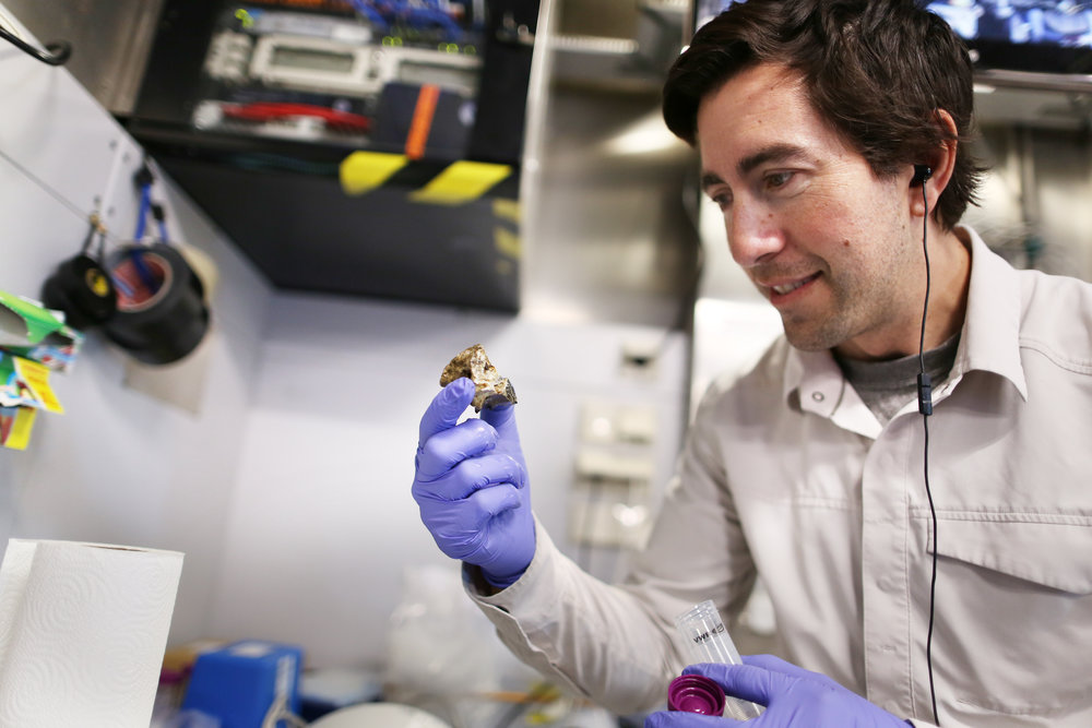 In the wet lab, Jeffrey Marlow examines one of the geologic samples brought to the surface by Remotely Operated Vehicle SuBastian's deployments in the Southern California Borderland.