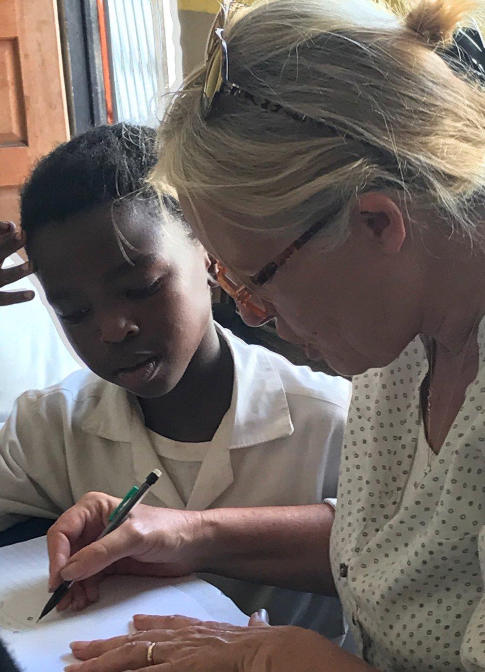 Alisonhelps Sibahle Kobese with her homework.