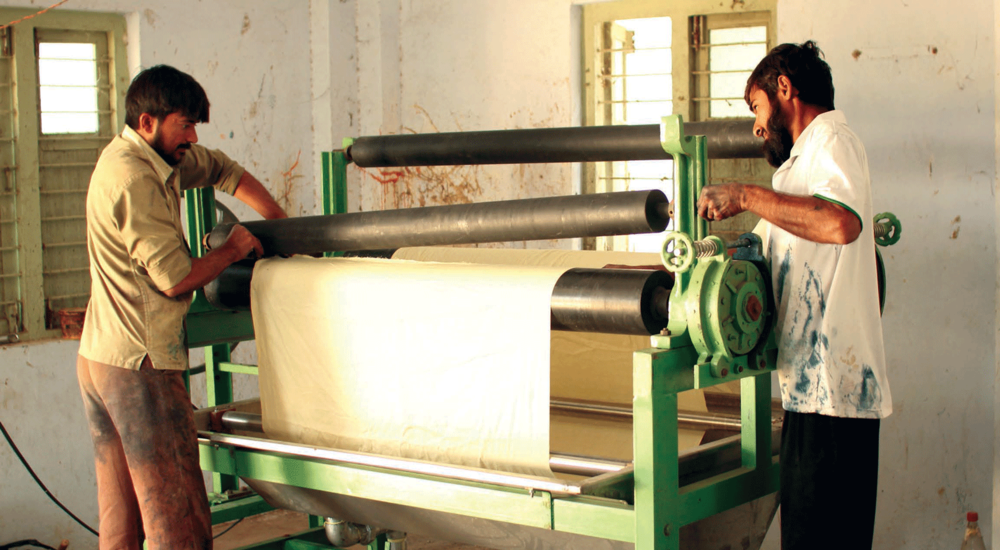 Block printers from Ajrakhpur exploring the use of a machine to treat the fabric with  Harde , a practice usually done manually