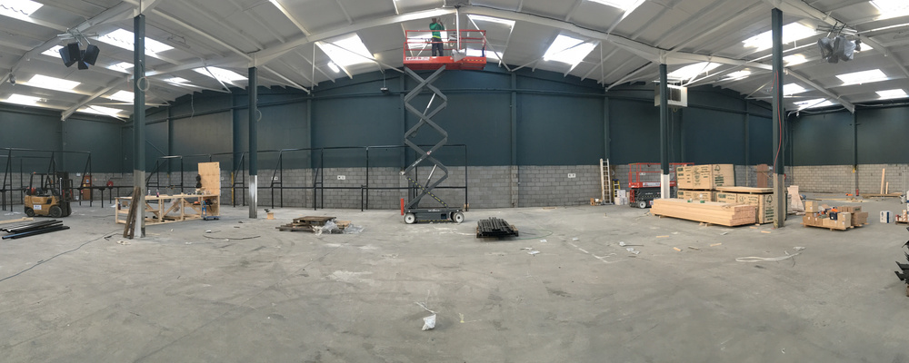 Ceilings being painted transforming an empty storage warehouse into Jump Evolution Indoor trampoline park in Romford Essex