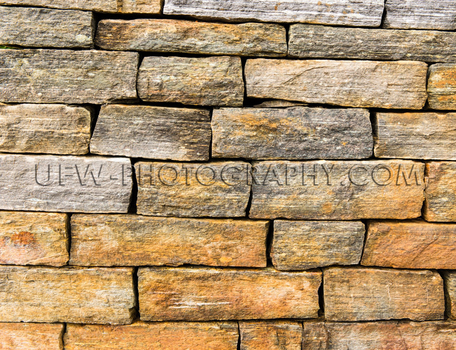 Golden gray stone wall blocks stacked full frame background Stoc