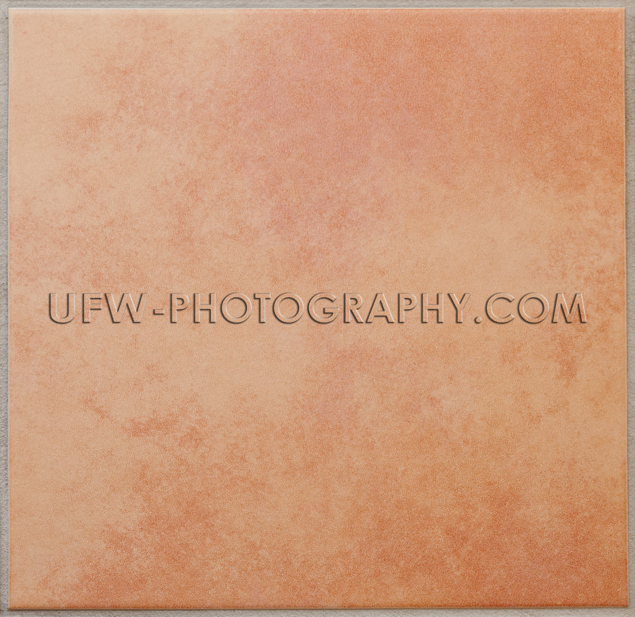 Single apricot colored ceramic tile textured full frame Stock Im
