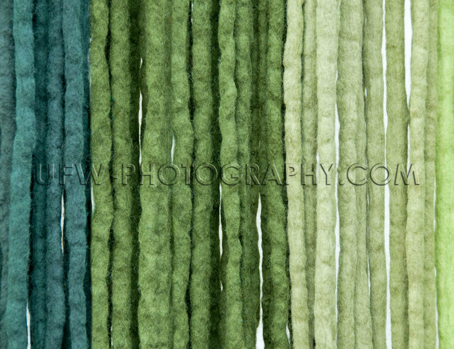 Felt ribbons blue green colored vertical strings background Stoc