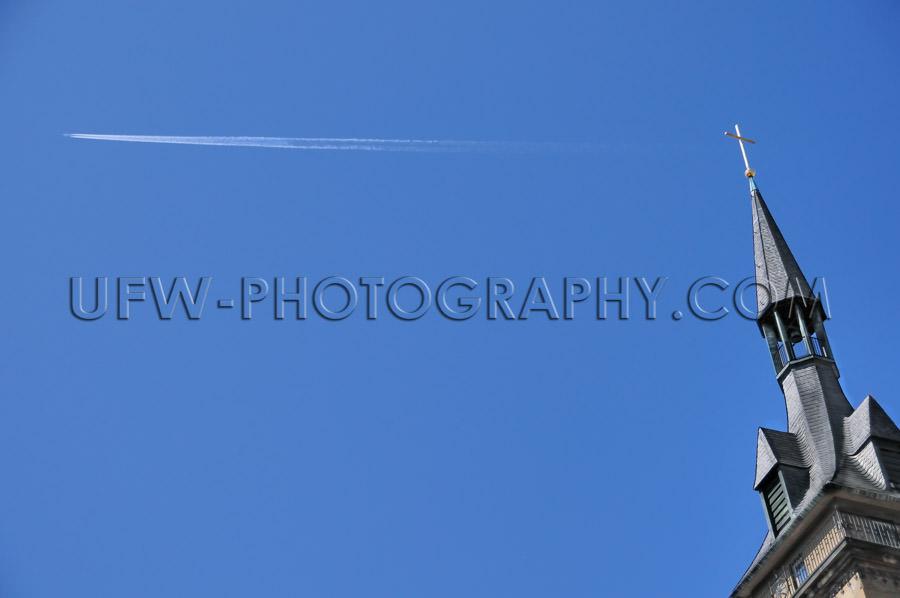 Church steeple, golden cross, jet stream against deep blue sky -