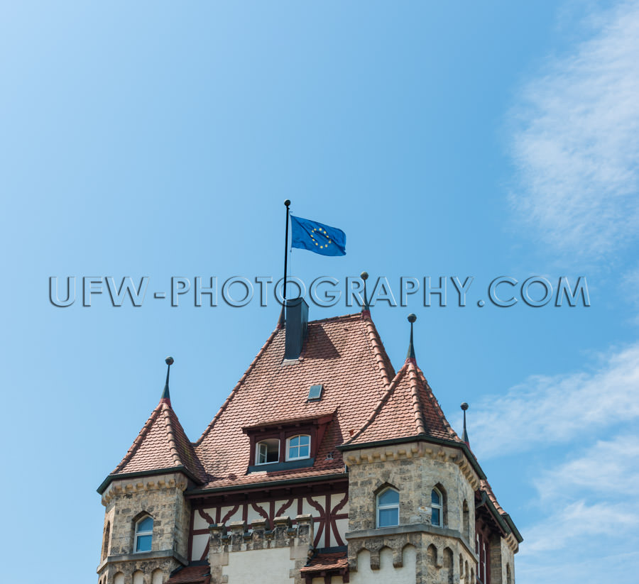 European flag waving top old building roof castle blue sky Stock