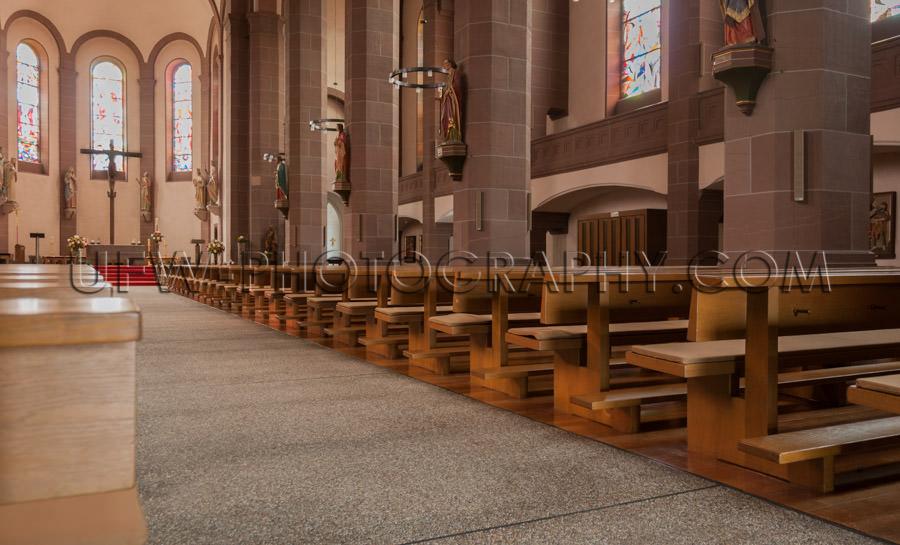 Inside church view rows benches aisle altar cross saint statues