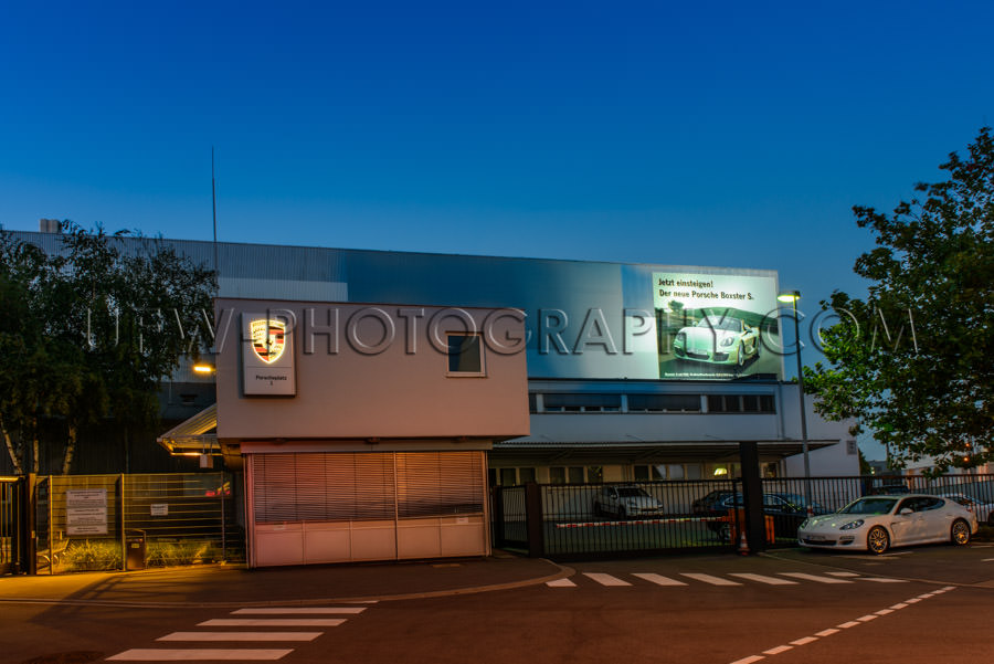 Porsche company headquarters gate car factory Germany night Stoc