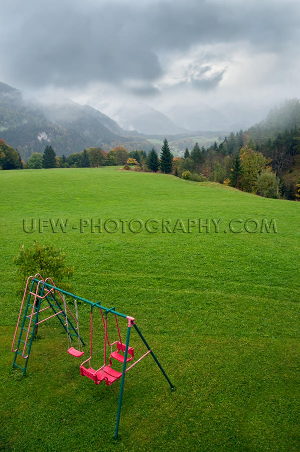 Green mountain pasture dramatic sky playground swing red Stock I