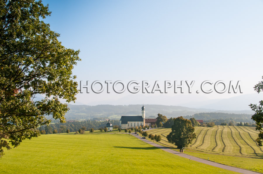 Idyllic sunny landscape baroque church field mountain trees Stoc