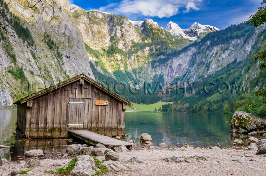Mountain lake fishing hut surrounded high mountain-range Stock I
