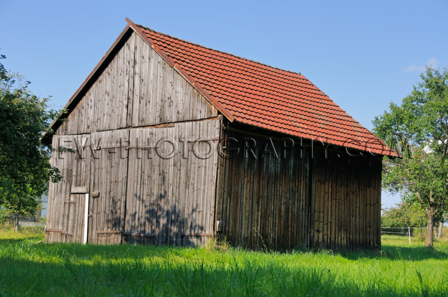 Wooden barn under blue sky with meadow and trees Stock Image