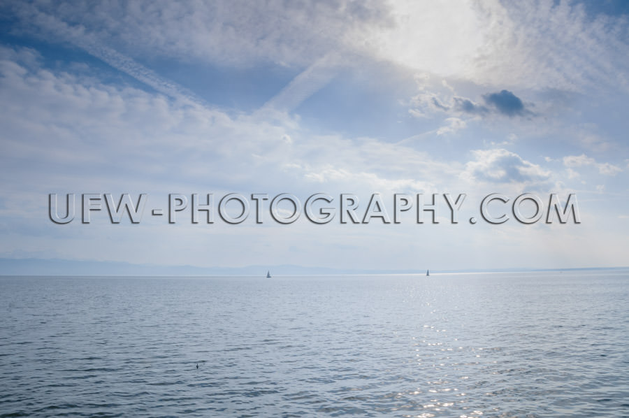 Blue lake sea view dramatic blue cloudy summer sky horizon Stock