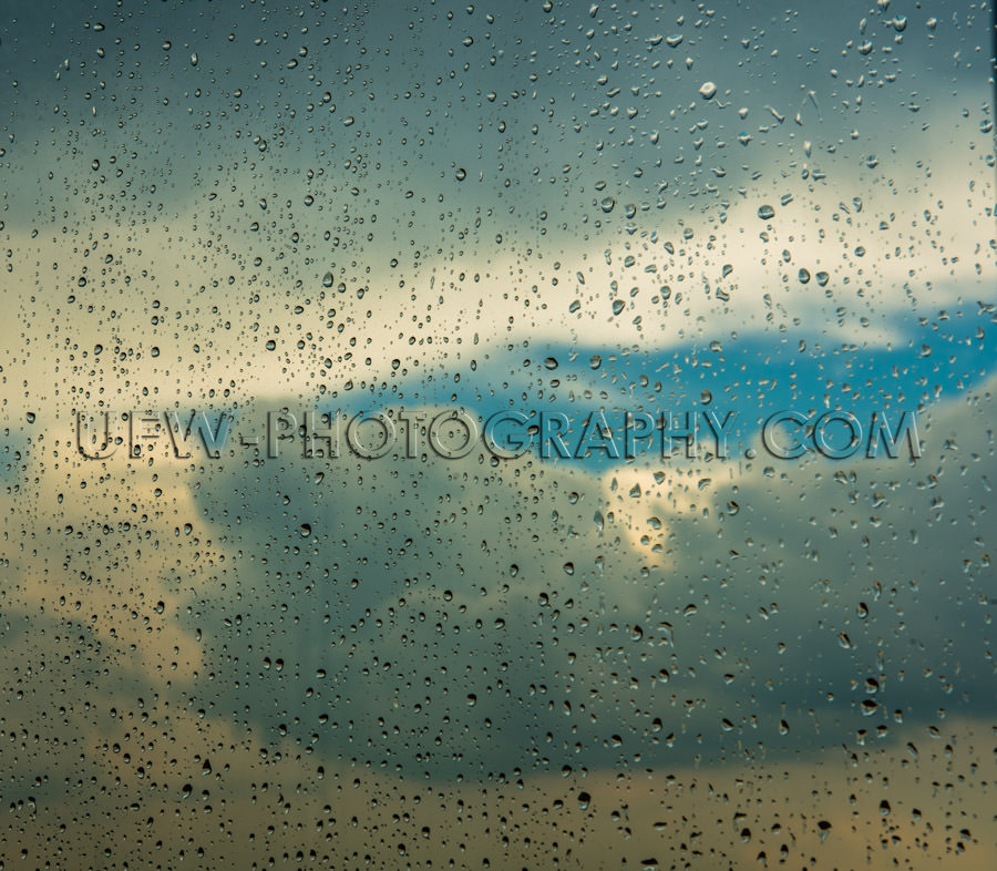 Raindrops window cloud sky blue patch rainy day Stock Image