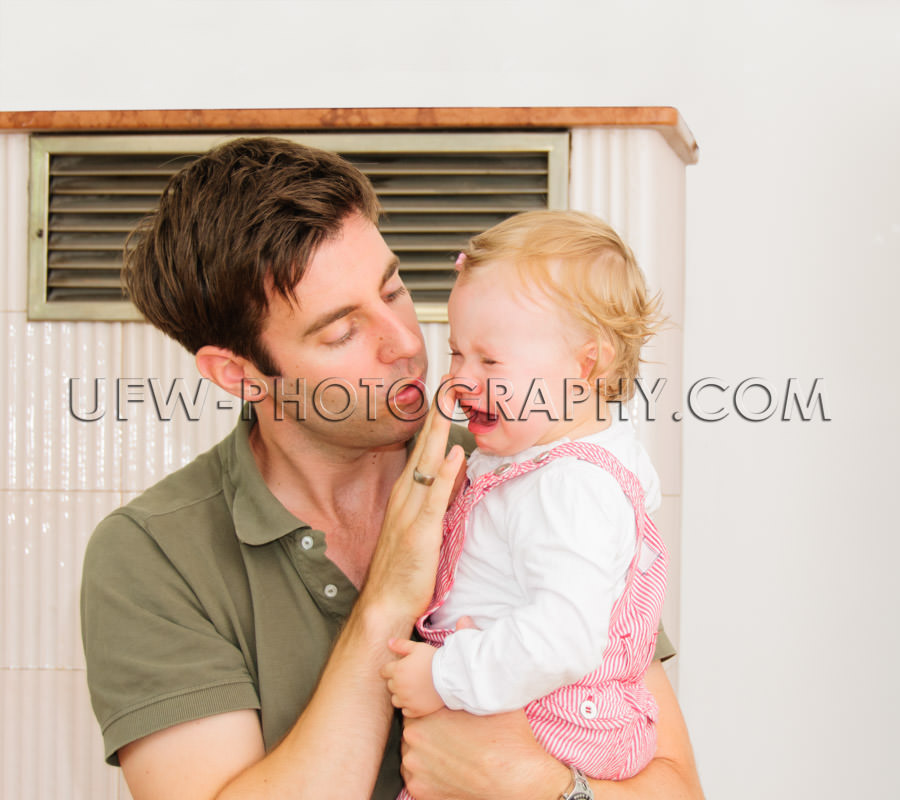 Crying girl toddler lovely young father caring one-year-old Stoc