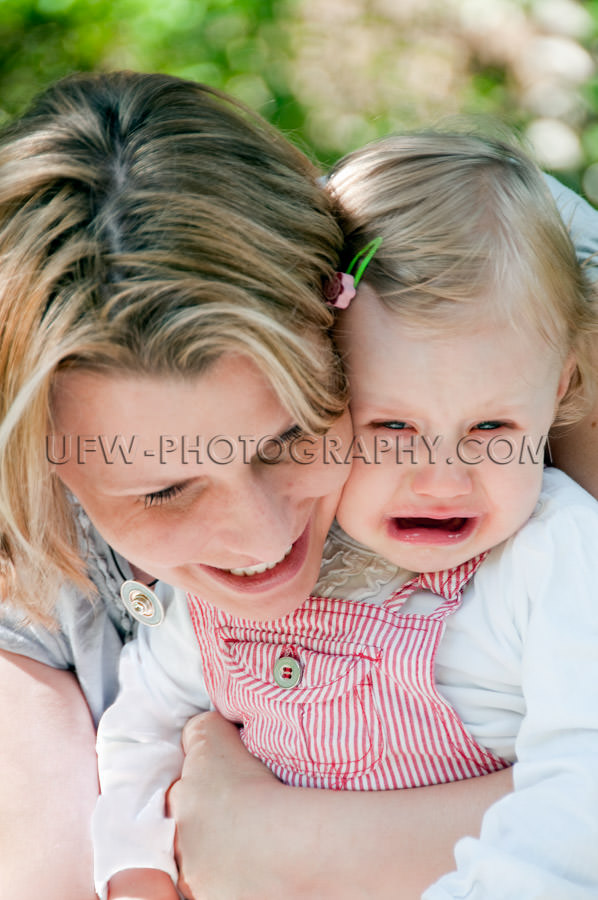 Crying one year old sad girl child comforted loving mother Stock