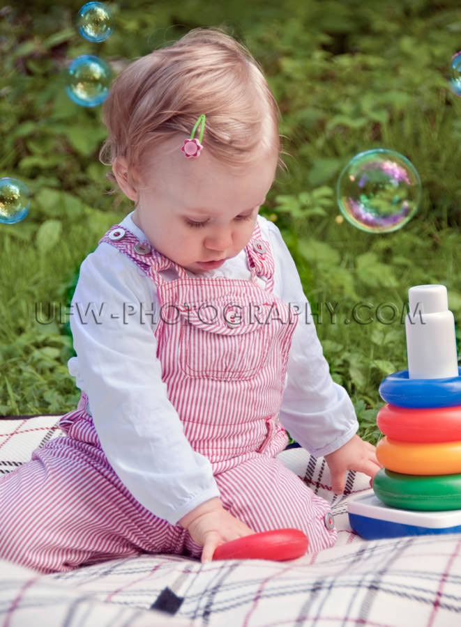 Cute little child toddler playing soap bubbles blanket green gar