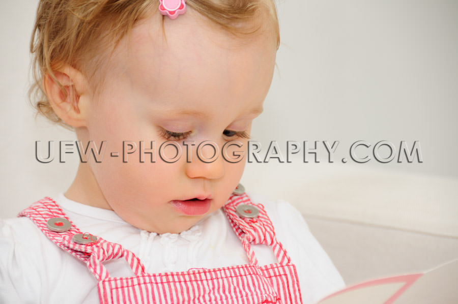 Cute little toddler girl reading card looking down sofa Stock Im