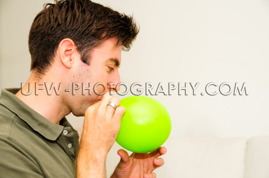 Dad blowing green balloon inflating close-up indoors casual Stoc