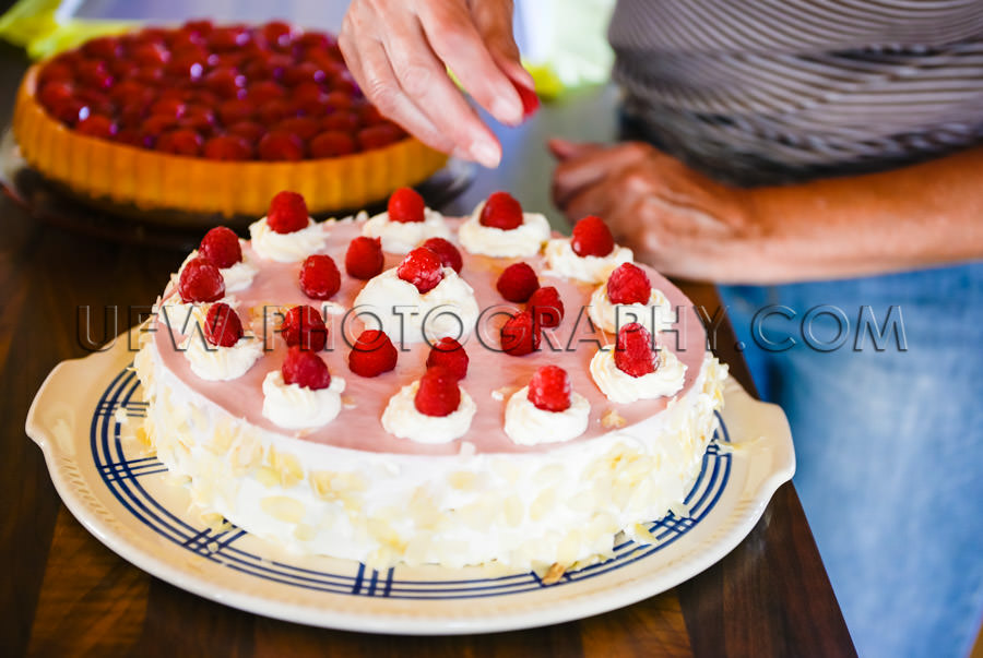 Decorating delicious raspberry cream cake kitchen woman hand Sto