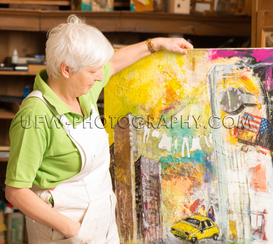 Female artist standing shows painting art studio Stock Image