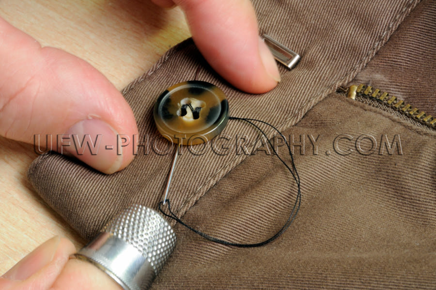 Fingers sewing on button thimble needle thread cotton pants Stoc