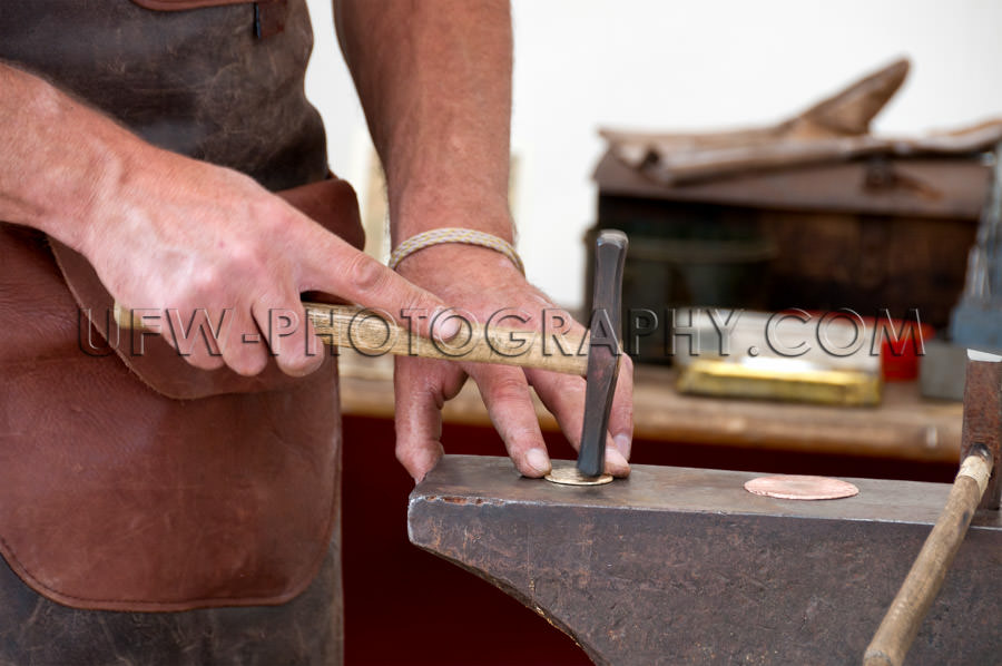 Goldsmith hammering human hand anvil flat sheet metal Stock Imag