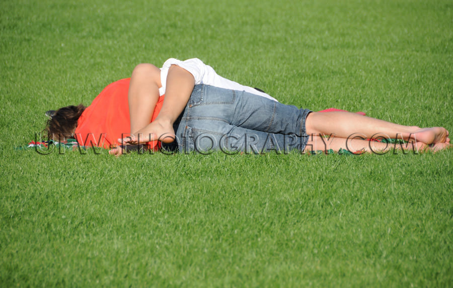 Lovely young couple lying green grass sleeping relaxing love tog