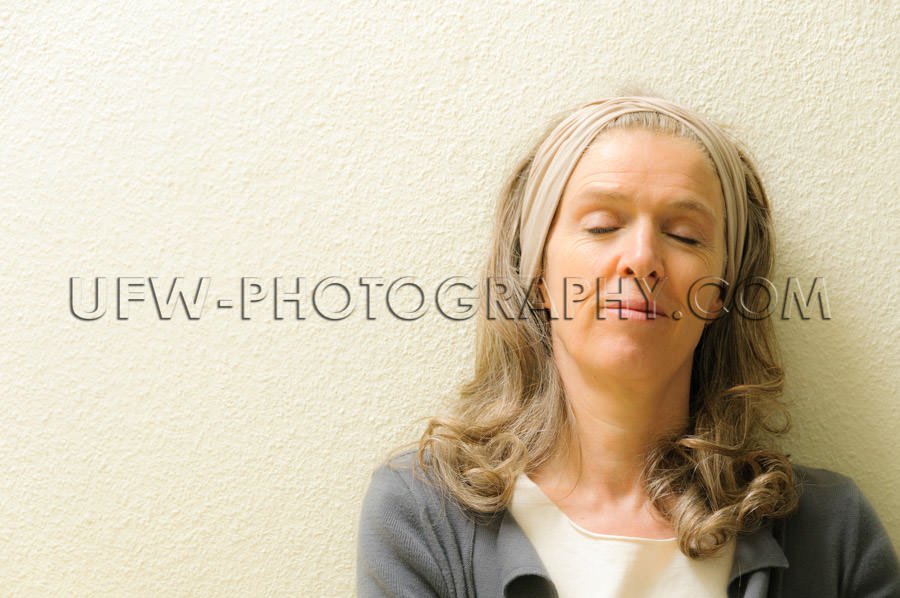 Mature woman eyes closed dreaming serenity leaning content Stock