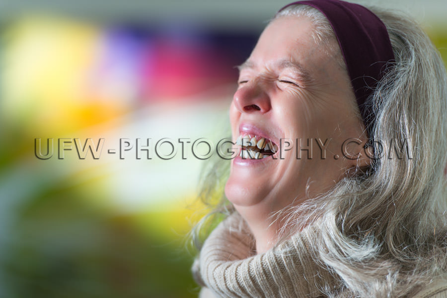 Mature woman laughing portrait head-wrap colorful background Sto