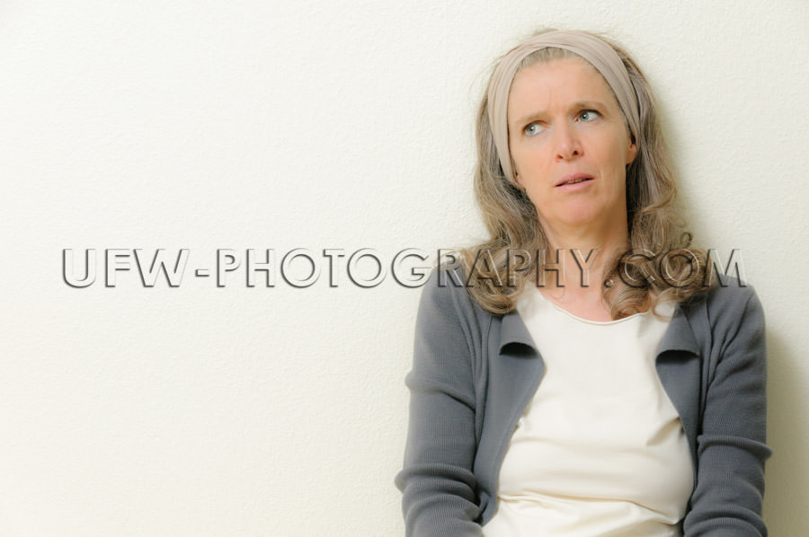 Mature woman pondering leaning wall head-wrap looking up Stock I